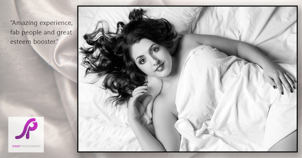 boudoir client testimonial shot from above lying on bed covered by white sheet