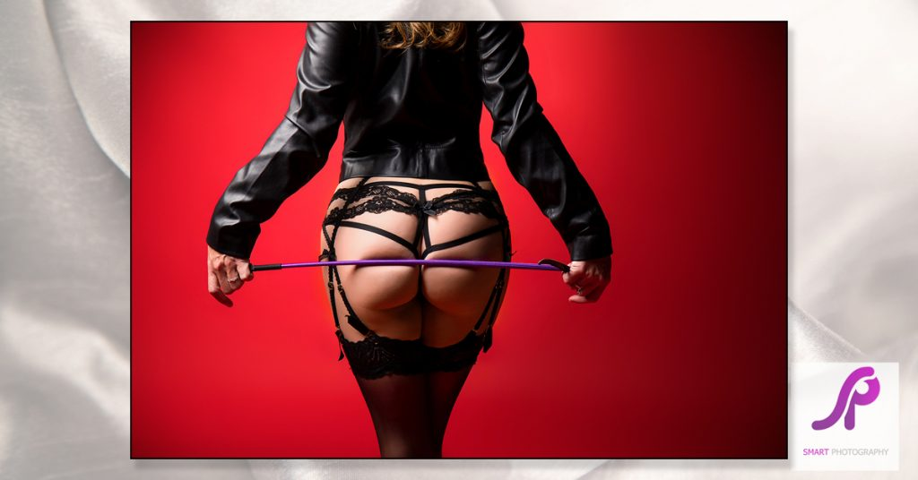show of womans back holding riding crop across bum wearing leather jacket