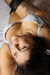 boudoir portrait on bed set posed on elbows arching back and looking into distance