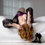 head over edge of bed set boudoir pose wearing black lace robe